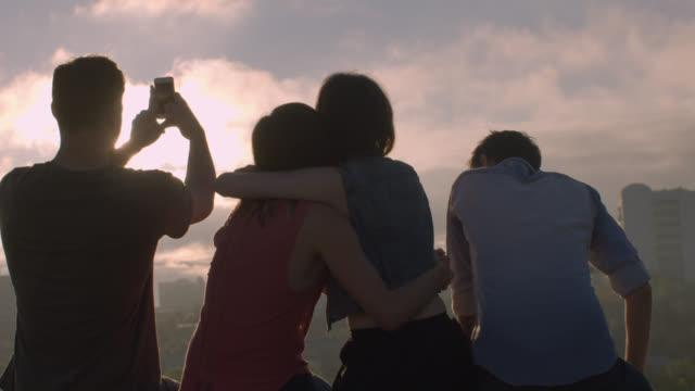 Group of friends hug and take smartphone photos over city skyline