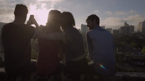 vídeos y material grabado en eventos de stock de group of friends hug and take smartphone photos overlooking austin, texas - tejado