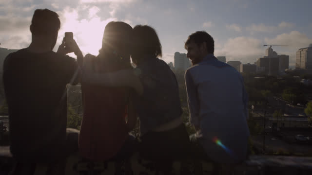 group of friends hug and take smartphone photos overlooking austin, texas - dach stock-videos und b-roll-filmmaterial
