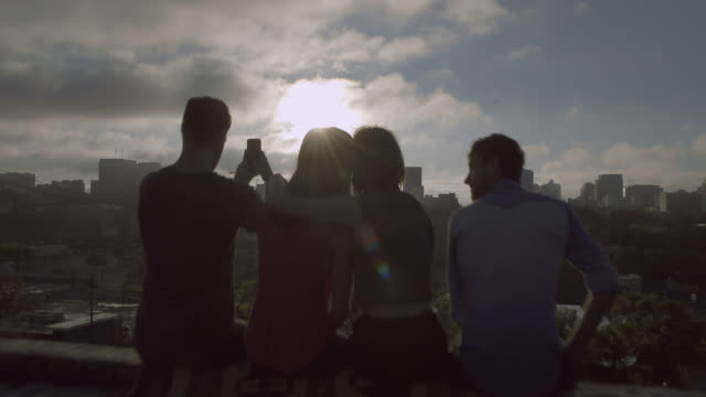 group of friends hug and take smartphone photos overlooking austin, texas skyline - roof stock videos & royalty-free footage
