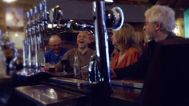 group of friends in 50s and 60s drinking and chatting at bar in pub - english culture stock videos & royalty-free footage