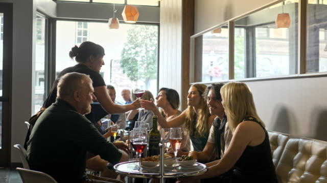 a group of friends in a wine bar cafe being served. - wine bar stock videos & royalty-free footage