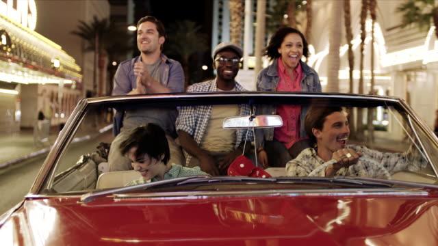 group of friends in classic convertible go wild in the streets of downtown las vegas - cabriolet bildbanksvideor och videomaterial från bakom kulisserna