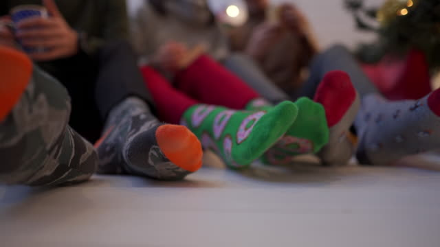 group of friends in cozy christmas socks relaxing - sock stock videos & royalty-free footage