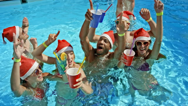 SLO MO Group of friends in the pool holding their drinks and waving into the camera with Santa hats on their heads