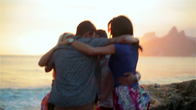 Group of friends jump around in a circle on Ipanema Beach at sunset