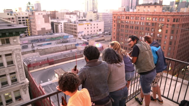 Group of friends leaning over a balcony in Downtown LA