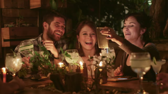 a group of friends look at a mobile phone / medellin, colombia - social gathering stock videos & royalty-free footage