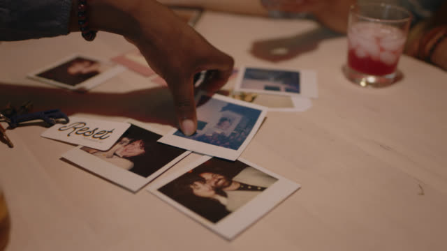 cu. group of friends look at instant photographs while sitting around kitchen table. - polaroid stock videos & royalty-free footage