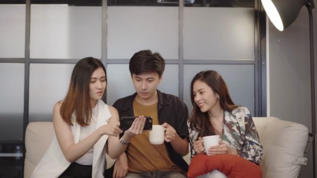 vídeos de stock, filmes e b-roll de grupo de amigos que olham o telefone esperto - portable information device
