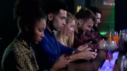 Group of friends networking on phones in nightclub