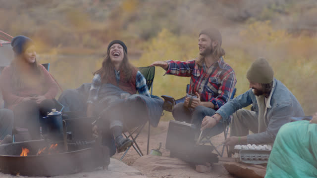 group of friends on camping trip talk and laugh by the fire as young man scrambles eggs in skillet. - lagerfeuer stock-videos und b-roll-filmmaterial