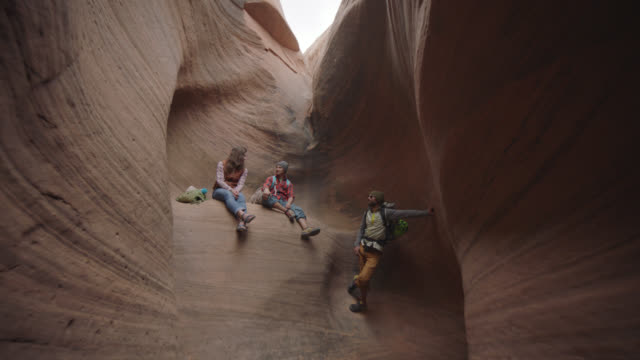 Group of friends on Moab climbing trip take a break on sandstone wall in beautiful slot canyon.
