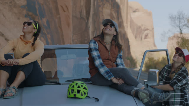 group of friends on moab road trip look up at climbers on the rock face and cheer them on. - 見上げる点の映像素材/bロール