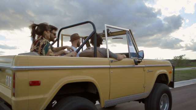 Group of friends on road trip talk and laugh in classic Ford Bronco