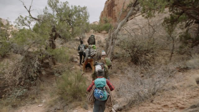 group of friends on rock climbing trip walk up mountain trail with backpacks and gear. - erforschung stock-videos und b-roll-filmmaterial
