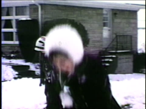 vídeos de stock, filmes e b-roll de a group of friends play in the snow. - 1960