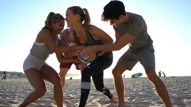 group of friends playing at the beach trying to grab the ball from beautiful woman - leisure activity stock videos & royalty-free footage