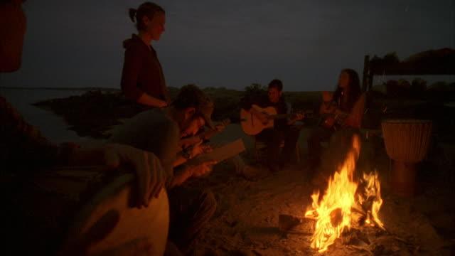 vídeos de stock e filmes b-roll de ms, group of friends  playing guitars and singing around beach campfire, cow island, maine, usa - fogueira de acampamento