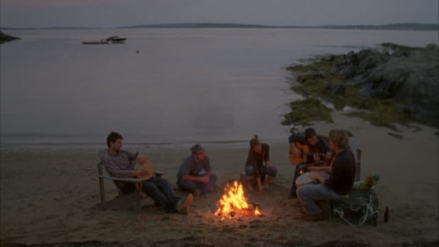 WS, HA, Group of friends  playing guitars around beach campfire, Cow Island, Maine, USA