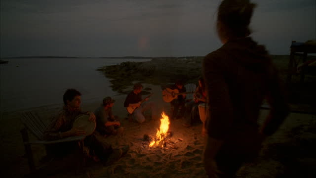 WS, HA, Group of friends  playing guitars around beach campfire, Cow Island, Maine, USA