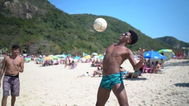 vídeos de stock e filmes b-roll de group of friends playing soccer at the beach - brasil