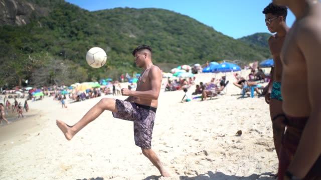vídeos y material grabado en eventos de stock de grupo de amigos jugando al fútbol en la playa - barra futbol
