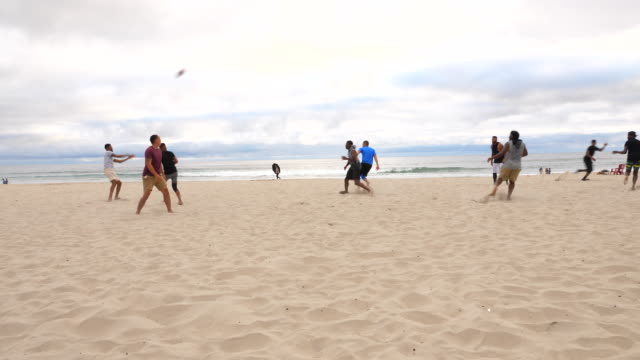 ws group of friends playing touch football game on beach on summer evening - touch football stock videos & royalty-free footage