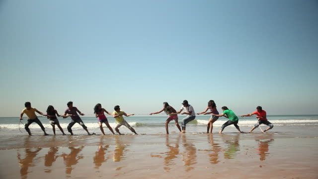 vidéos et rushes de group of friends playing tug-of-war on the beach - corde