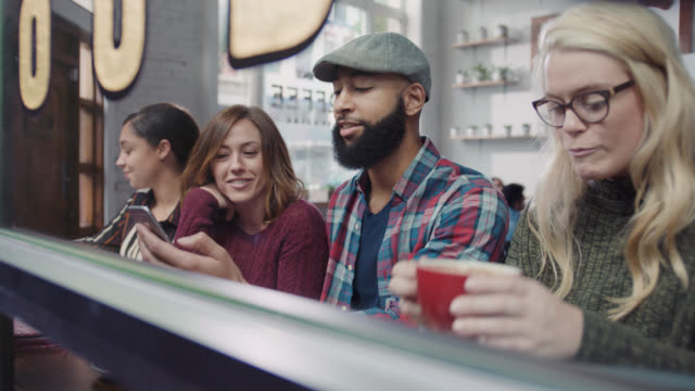 WS. Group of friends point at smartphone and laugh in local coffee shop window.