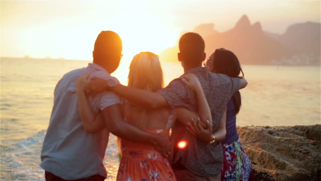 Group of friends point to the sunset, talk and laugh on Ipanema Beach