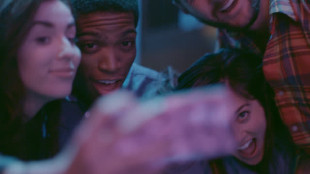Group of friends pose for crazy selfies in nightclub in slow motion