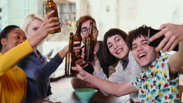 group of friends posing for a group selfie with beer bottles - vanguardians stock videos & royalty-free footage