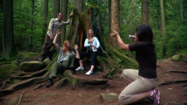 group of friends posing for pictures in front of large moss-covered tree trunk during hike - kelly mason videos stock videos & royalty-free footage