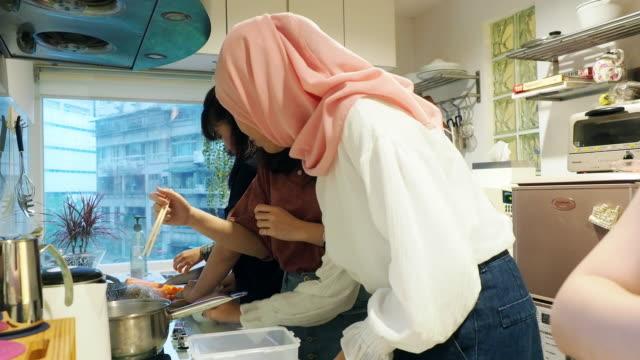 vidéos et rushes de groupe d'amis préparant le dîner ensemble dans la cuisine - origine ethnique
