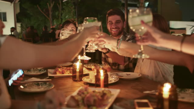 a group of friends raise glasses in a toast / medellin, colombia - speisen stock-videos und b-roll-filmmaterial
