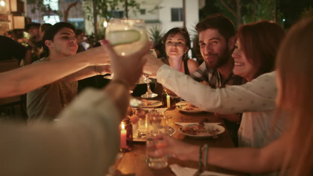 stockvideo's en b-roll-footage met a group of friends raise glasses in a toast / medellin, colombia - viering