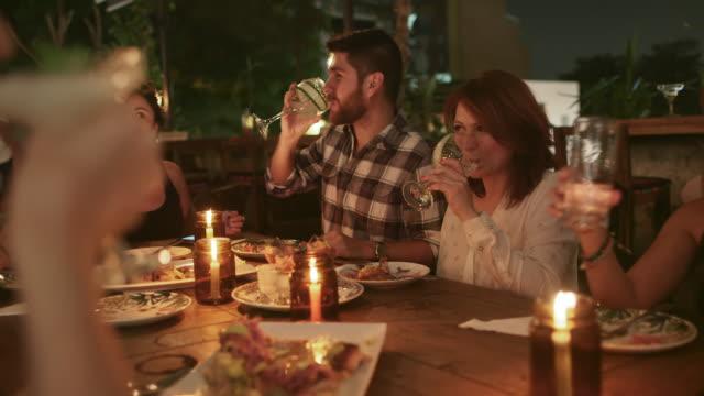 vídeos de stock e filmes b-roll de a group of friends raise glasses in a toast / medellin, colombia - brinde