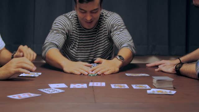 Gruppe von Freunden entspannen und spielen Karten zusammen zu Hause.