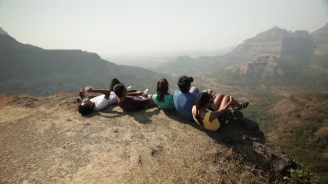 vídeos y material grabado en eventos de stock de group of friends relaxing on a cliff of mountain - manos detrás de la cabeza