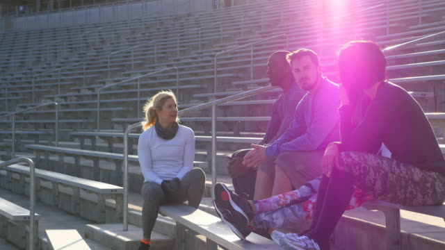 MS Group of friends resting on bleachers during workout in stadium at sunset