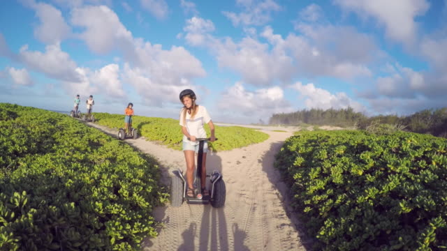 stockvideo's en b-roll-footage met a group of friends ride segways together on the beach - oahu