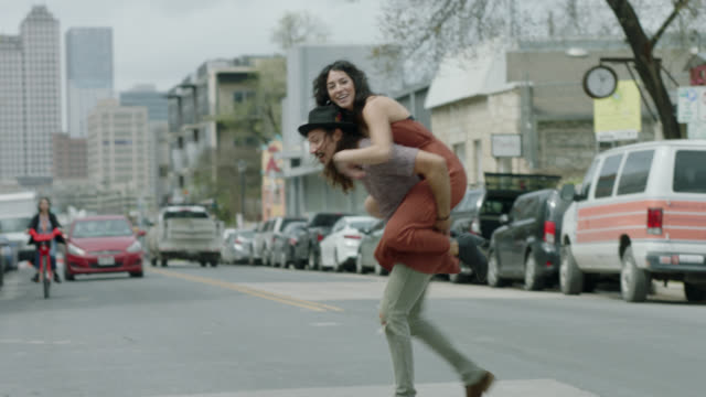 vídeos de stock, filmes e b-roll de group of friends run to cross austin city street and woman hops onto man's shoulders for piggyback ride in front of oncoming traffic. - vida urbana
