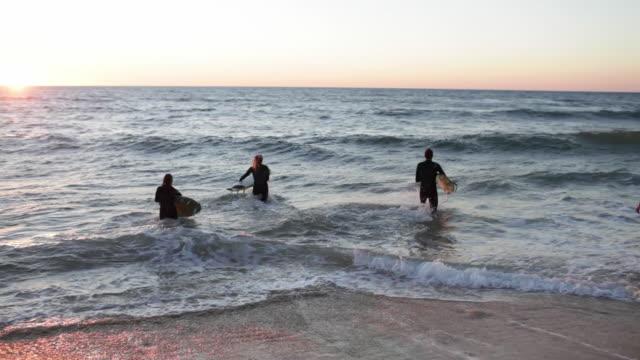 group of friends running, jumping into ocean, paddling on surfboards - surfen stock-videos und b-roll-filmmaterial