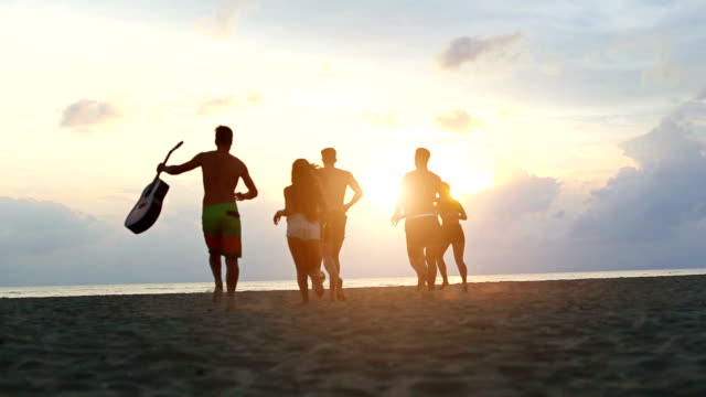 group of friends running on the beach at sunset - party social event stock videos & royalty-free footage