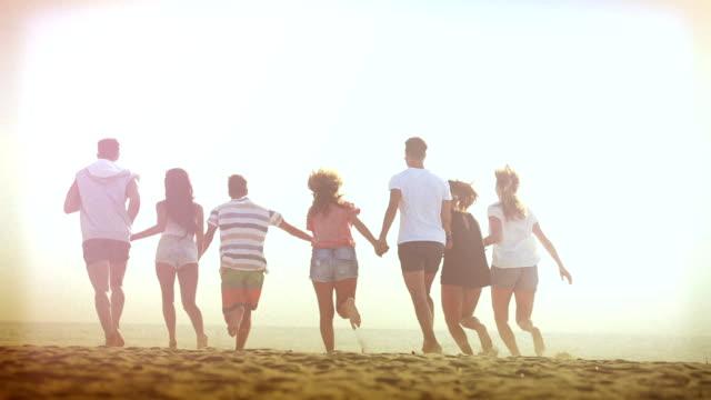 Groep vrienden lopen op het strand bij zonsondergang