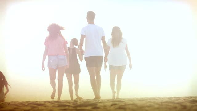 vidéos et rushes de groupe d'amis courir sur la plage au coucher du soleil - 16 17 ans