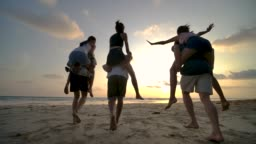 SLOW MOTION - Group of friends running on the beach at sunset with happy emotion. People with party celebration concept. Back Rear View.