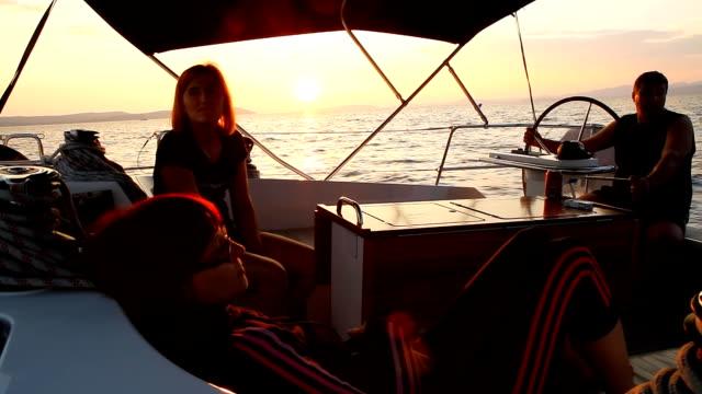 vidéos et rushes de groupe d'amis de voile au coucher du soleil - capitaine de bateau