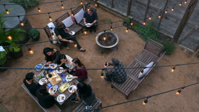 ha ms group of friends sharing food during backyard barbecue - courtyard stock videos & royalty-free footage